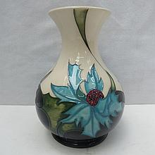 A Moorcroft vase decorated with blue flowers.