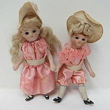 Two late 19th century miniature dolls each with hand painted faces, glass eyes, porcelain heads and