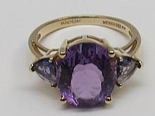 An oval mixed cut amethyst with two small trapeze