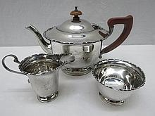 A three piece silver tea service, Birmingham 1939, the teapot of circular form with a shaped lip, turned wooden knop and brown bakelite handle, with milk jug and sucrier, 15ozt all in.