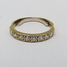 A diamond half eternity ring. Eight small brilliants, estimated weight .45cts, claw set in plain setting. Yellow precious metal, mark obscured by soldered clip.