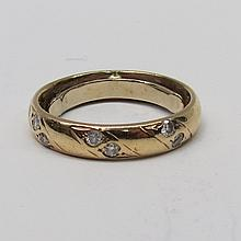 A yellow precious metal band set with three diagonal pairs of diamonds, a