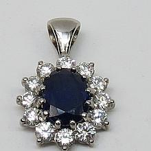 An oval sapphire and diamond cluster pendant. Central sapphire mixed cut, probably Sri Lankan, surrounded by gallery of twelve brilliant cut fine colour diamonds.