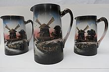 Three decorative jugs of graduated sizes,