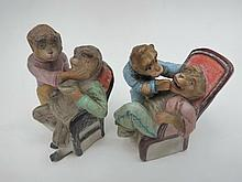 A pair of small comical figures of monkeys.