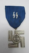 A Nazi SS medal, white metal swastika with oak