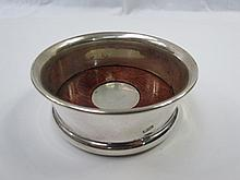 An HM silver wine bottle coaster bearing millenium