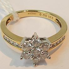 A seven stone daisy cluster ring, claw set with