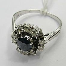 A sapphire and diamond cluster ring, the central