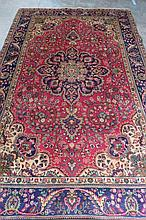 A traditional Tabriz rug, red ground with blue and