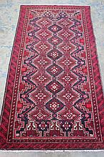 A Baluchi geometric style pattern rug, red ground