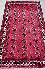 A traditional Baluchi rug, red ground with black,