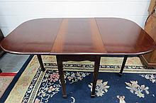 A mahogany drop leaf table raised over reeded
