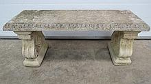 A carved stone bench raised on twin associated