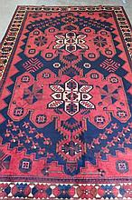 A Luri traditional rug, red ground with Aztec