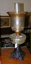 A Victorian oil lamp on cast iron base with glass