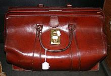 A leather Gladstone bag with brass lock plate
