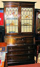 An oak bureau bookcase with lead glazed upper