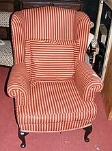 A winged easy chair upholstered in striped