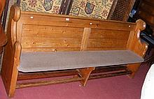 A pine pew with panelled back