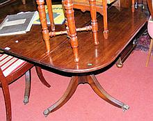 An antique mahogany dining table on twin pedestal