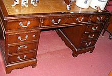 A reproduction pedestal desk with brown leather