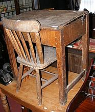 An old school desk with stickback chair