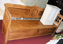 An antique stripped pine bench with lift-up hinged