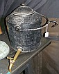 An old cast iron hanging kettle with brass spout