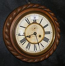 An eight day striking wall clock with oak rope twist surround