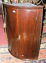 An antique bow front mahogany hanging corner cupboard