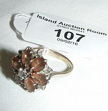 """A lady's attractive """"flower"""" ring with central diamond set in 18ct white go"""