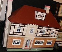 An old Hamleys of London large dolls house with two doors opening to fitted