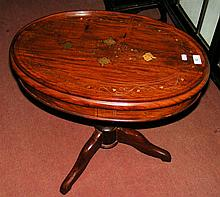 A decorative brass inlaid oval occasional table
