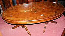 A decorative brass inlaid oval coffee table