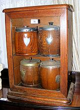 Four oak biscuit barrels contained within a glazed oak cabinet