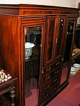 An Edwardian triple wardrobe, the cupboard and drawer section flanked by mi