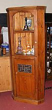 An antique pine corner cupboard