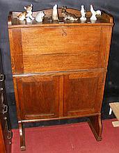 An oak student's bureau with cupboards below