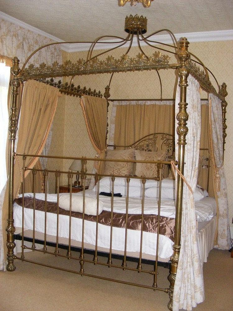 An ornate brass four poster bed with good quality