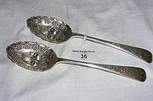 A pair of decorative Edwardian silver berry spoons