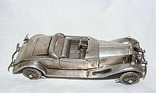 A 13cm silver model of an old open touring car