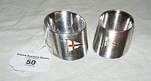 A pair of silver napkin rings with enamel yacht