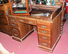 A mahogany roll-top desk with nine drawers to the