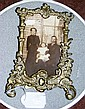 An ornately cast brass photo frame/stand
