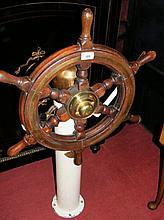 An old brass mounted ship's wheel on cast metal column - bearing maker's pl