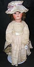 An old Simon and Halbig bisque head doll with glass eyes and open mouth, wi