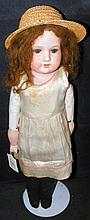 An old Armand Marseille bisque head doll with cloth body and glass eyes, wi