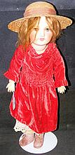 An old bisque head doll with rolling glass eyes and open mouth, having comp