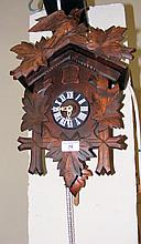 A carved wooden cuckoo clock with bird surmount